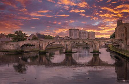 The Historic Old Bridge at Ayr in Scotland that spans the River Ayr and a spectacular red blazing sunset over the town.
