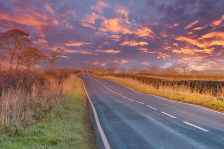 A two laned roadway in Scotland as the autumn takes hold and before the snow of winter arrives. There are brown and red autumn colours as the road goes off kinto the distance as the sun goes down with a red blazing sky