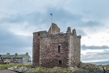 The ruins of old Portencross Castle while the Scottish Saltire Flag is flying proudly from its battlements on a bitter winters day Stock Photo