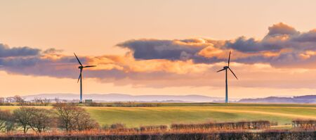 Two Wind Turbines on a cold Scottish Day in Autumn with green fields and hedges and a cloudy sky just as the sun was setting dramatic cloudy evening sky Stockfoto