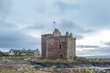 The ruins of old Portencross Castle while the Scottish Saltire Flag is flying proudly from its battlements on a bitter winters day