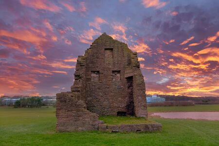 The remains of the old Engine House that served Auchenharvie Colliery in the Ayrshire town of Ardeer in Stevenston North Ayrshire Scotland at the sunset end of the day with a blazing red sky.