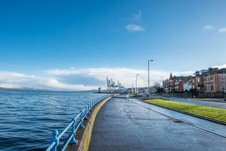 Greenock, Scotland, UK - January 19, 2018: Greenock's esplanade in the west end of the town looking over to the contrasting ClydePort Terminal with its port and heavy cranes. A contrasting scene between residential and industrial.