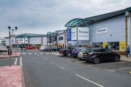 Irvine Riverway Retail Park, Scotland, UK - April 10, 2020: A long queu and controlled entry at Irvine Retail Park with people lined up to enter M&S FoodHall one at a time thirty maximum in store.  Scotlands measures taken in the fight against Covid-19. Editorial