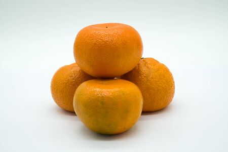 Four Satsuma Oranges on a white background. They Are not perfect but a realistic image of what you get in the shops.