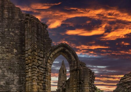 Looking through the  old stone entrance to The Old Transept Ancient Ruins and the dramatic sunset sky at Kilwinning Abbey Scotland. Stock Photo