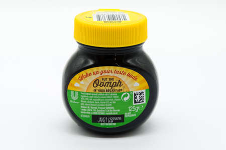Irvine, Scotland, UK - March 08, 2020: Marmite branded yeast extract in recyclable glass jar and recyclable plastic lid. Label displays the Unilever symbol the 'e'symbol and the recycling symbols.
