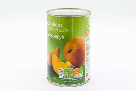 Irvine, Scotland, UK - March 08, 2020: Sainsbury's Branded  Peach Slices in recyclable tin can and lid. Label displays Kcal and energy values and 'e' symbol. Recycling Symbol and vegetarian 'V' symbols are also displayed on label.