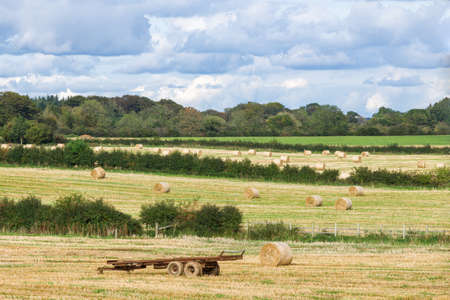 Perceton Irvine Scotland looking over typical Ayrshire farmlands with a trailer and round bales of hay. 免版税图像