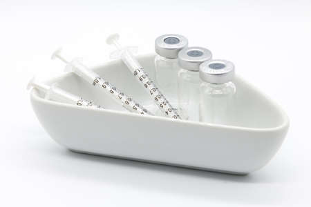 Three Medical vaccine syringes and Three medical ampules in a medical ceramic dish on a white background.