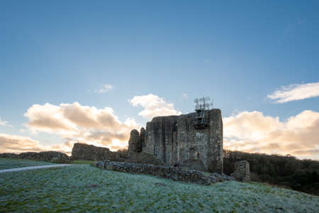 Dundonald, Scotland, UK - December 30, 2020:  Dunonald with its ancient castle still under renovation with scaffolding being seen next to the flag pole. Castle closed to public due to covid.