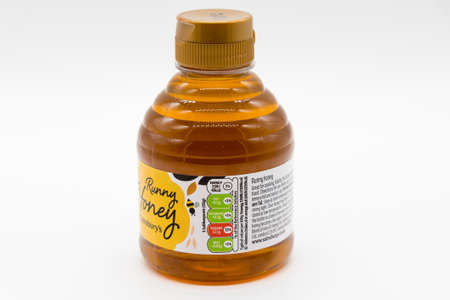 Irvine, Scotland, UK - January 09, 2021: Sainsbury's Branded bottle of Runny Honey in a bottle and cap that is recyclable. Paper labels displaying symbols and information. 免版税图像 - 161917232