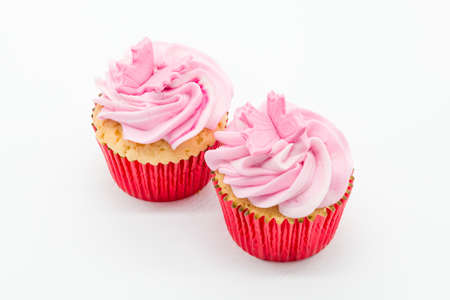 Easter cup cakes two in number with pink icing and red sponge casings on a white background.