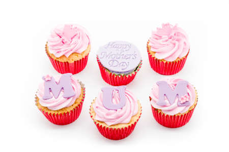 Six cup cakes with pink icing and red sponge casings on a white background. With Happy Mother's day and MUM written across the cakes