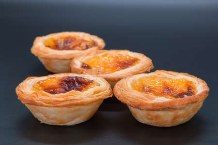 Four small custard tarts on a dark grey background. selective focus on the front two tarts and softens through the view of the image.