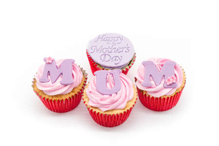 Three cup cakes with pink icing and red sponge casings on a white background. With Happy Mother's day and MUM written across the cakes