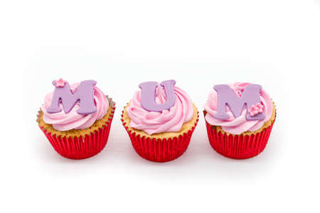 Three cup cakes with pink icing and red sponge casings on a white background. With MUM written across the cakes