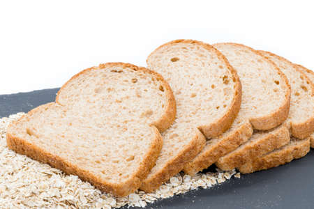 Five slices of oatmeal bread on a bead of oats on a white background. Produce of many farming communities in Scotland. 免版税图像