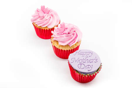 Three cup cakes with pink icing and red sponge casings on a white background. With Happy Mother's Day on the front cup cake
