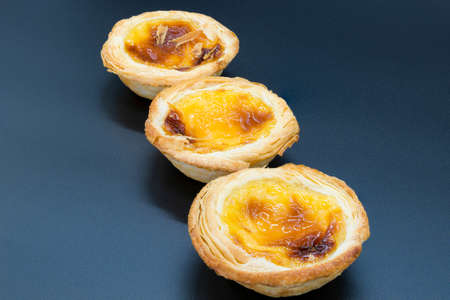 Three small custard tarts on a dark grey background.