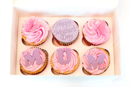 A selection box of Mother's Day cup cakes six in number with happy Mothers day on one of the cakes and MUM spelled out on each of the cakes.