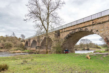 Gatehead, Irvine, Scotland, UK - March 23, 2021: Laigh Milton Viaduct is thought to be the Oldest surviving Public railway viaducts and its ancient stone detail. It is a category A listed structure which was built for the Kilmarnock and Tron railway in 18 新闻类图片