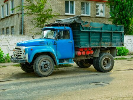 An old dump truck stands on the side of the road Banque d'images