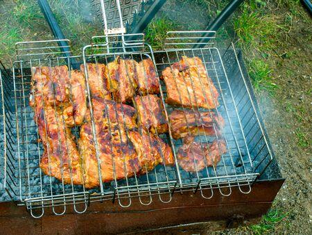 把肉放在烤架上烤的过程,特写。烤肉,在夏天的网格上。