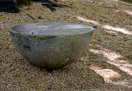 Hemispherical concrete seat in a bed of river rock