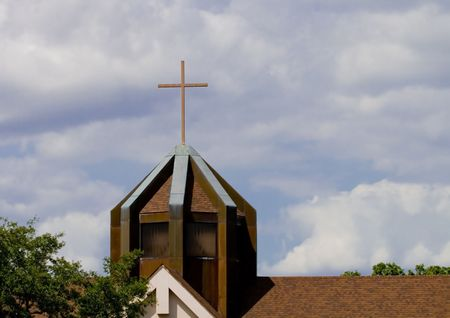 Church roof and steeple against a cloudy sky