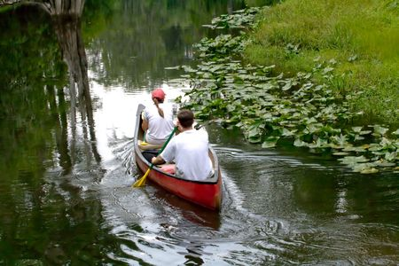 People in canoe near the river bank