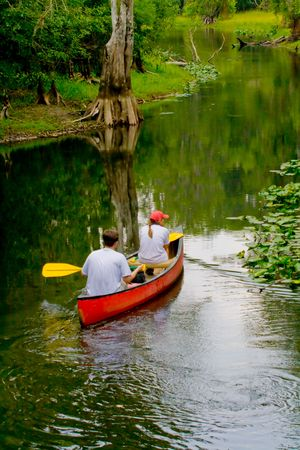 People in canoe approching a bend in the river