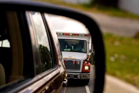 View of ambulence approaching in side view mirror