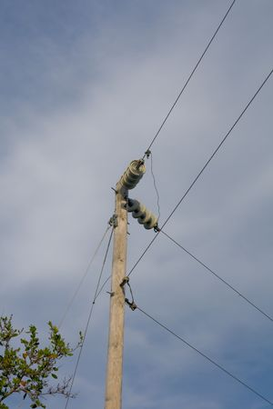 routed: Power lines making a routed turn on pole against sky