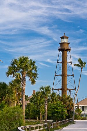 Sanibel, FL lighthouse  on western end of island against sky to the right in image with palm trees