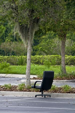 Office chair in the middle of a parking lot