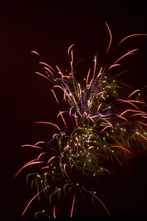 Multiple firey red bursts with blue sparks flying upwards photo