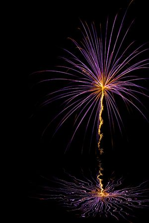 newyears: Purple burst with orange center and tail trailing below over water Stock Photo
