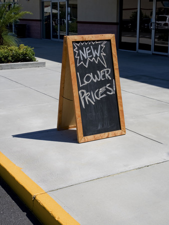 Blackboard sign that says lower prices on sidewalk Stock Photo