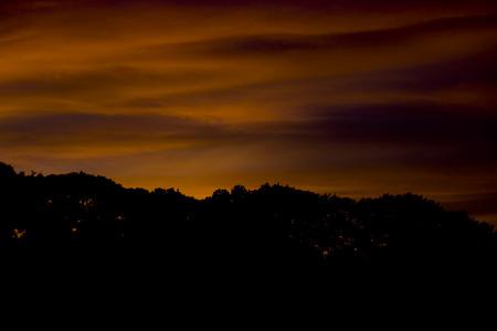Spooky looking red-orange sky over a dark silhouette of the treeline