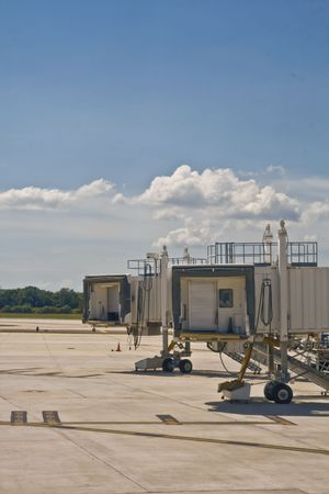 runways: Airport jetway retracted against taxiway and runways