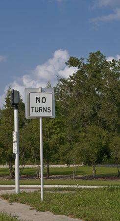 No turns sign at intersection with trees in background