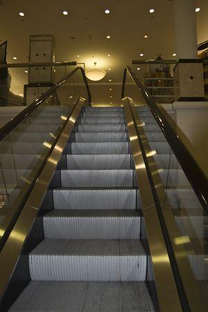 ソフト金色の色合いで上向きに主要なデパートのエスカレーター 写真素材