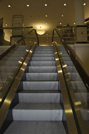 Escalator in a department store leading upwards in a soft golden hue