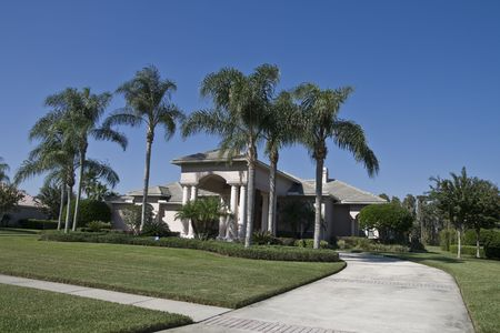 House with palm trees from street showing driveway and sidewalk Stock Photo