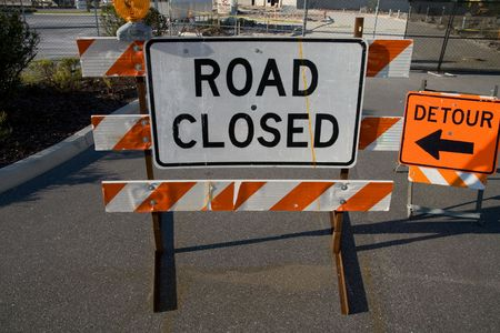 Road closed and detour signs on road barriers Stock Photo