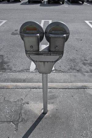 Parking meters in the sidewalk next to parking lot Stock Photo