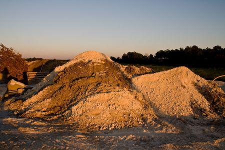 heaping: Heaps or several types of gravel in the golden light of dusk