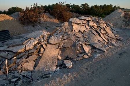 Pile of road scraps on construction site in the long shadows of the late afternoon Stock Photo