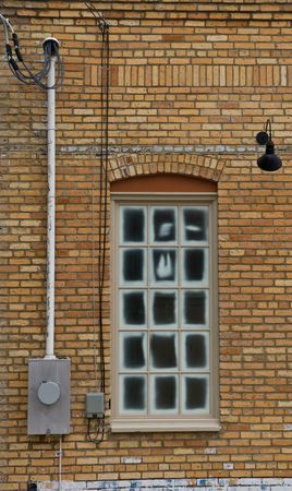 meter box: Window in a yellow brick wall with lights on wall and meter box